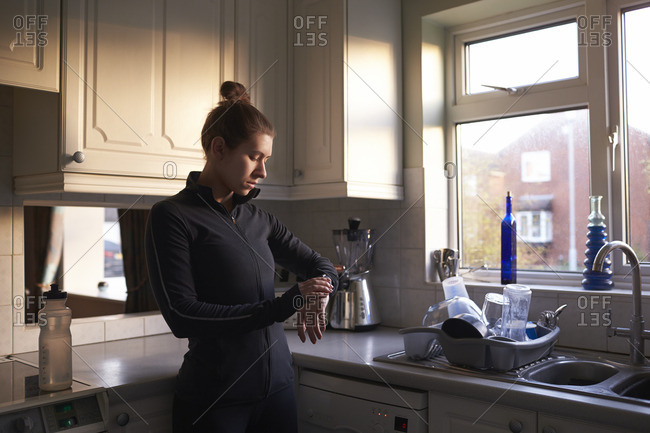 Woman At Home Checks Activity Tracker Before Exercise