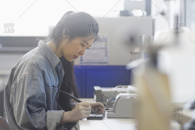 Female technician soldering electronic components in an industrial plant
