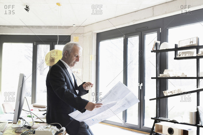 Senior businessman looking at blueprint in the office