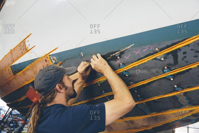 Seattle, Washington, 7/27/15: Man repairing boat bottom