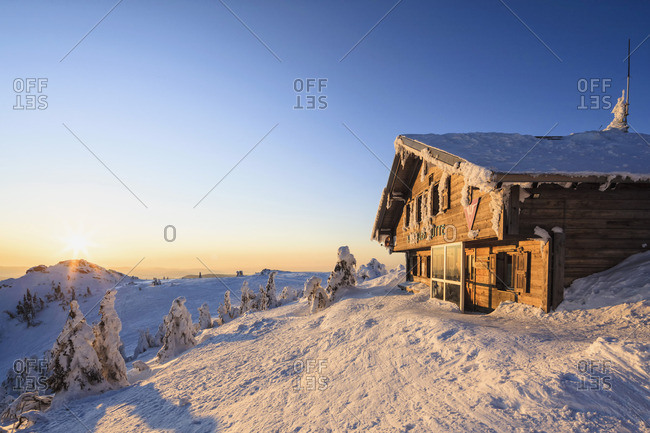 Germany- Bavaria- View of snow covered mountain hut at Bavarian Forest
