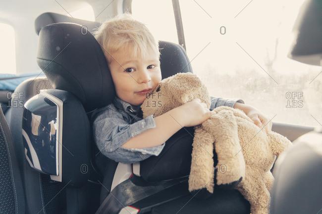 Germany- Little boy sitting in back-seat car seat