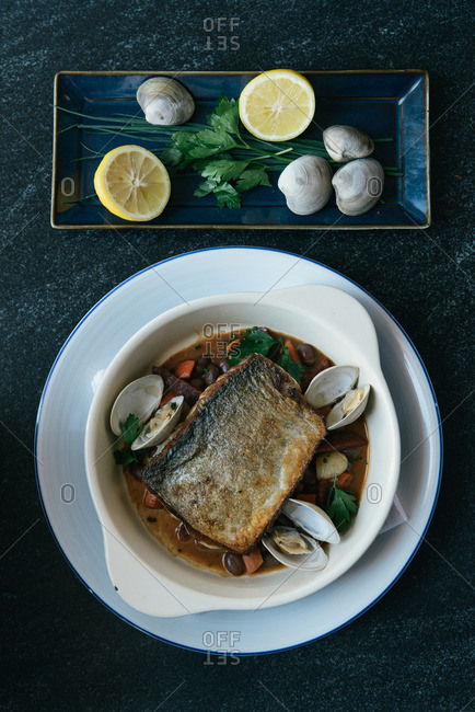 Filet of fish and clams served in broth