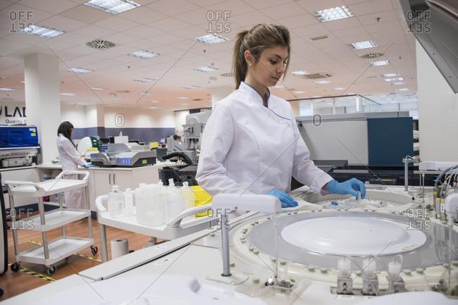 Laboratory technician in analytical laboratory using autoanalyzer