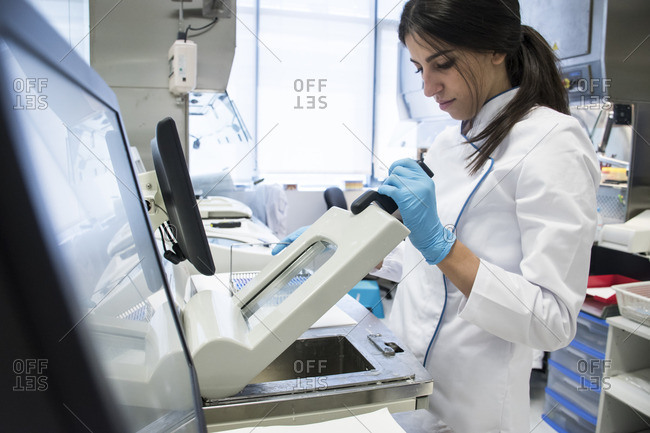 Laboratory technician in analytical laboratory using a cytology scanner