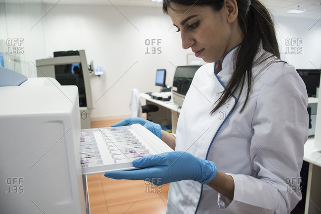 Laboratory technician in analytical laboratory putting object plates in cytology reader