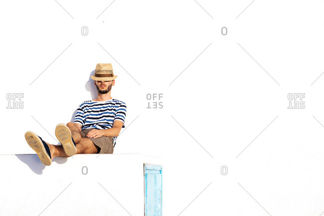 Man with straw hat and striped t-shirt sitting on spur leaning against white wall