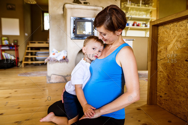 Little boy embracing his pregnant mother at home