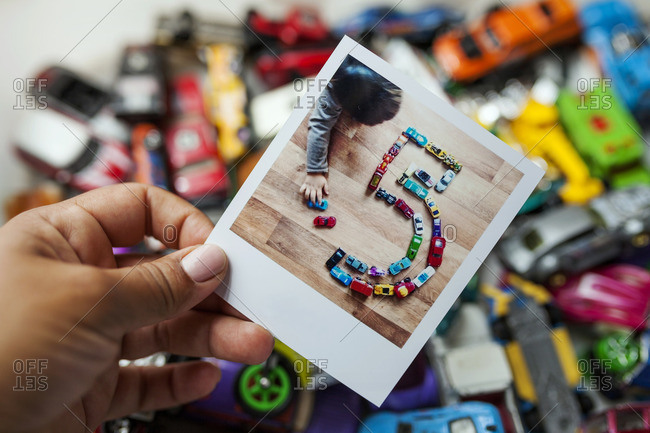 Photo of a little kid playing with his cars making a number five