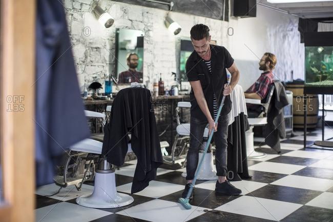 Barber sweeping in barber's shop