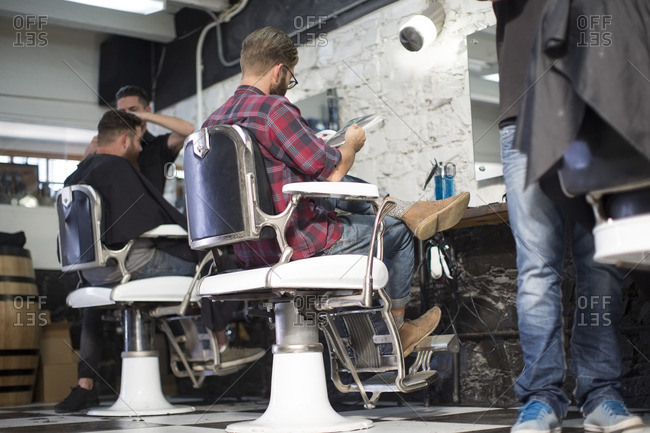 Customer reads magazine while seated at the barbershop