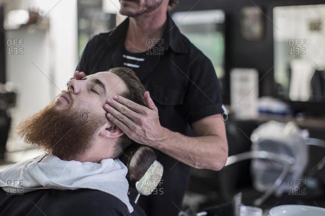 Barber measures on customers head before haircut at the barbershop