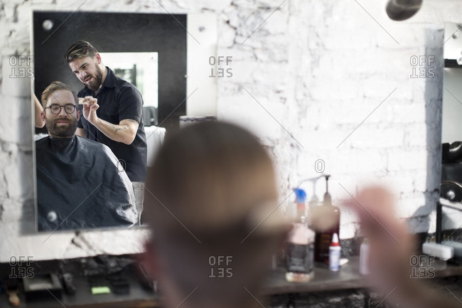 Barber and customer- barber combs his hair