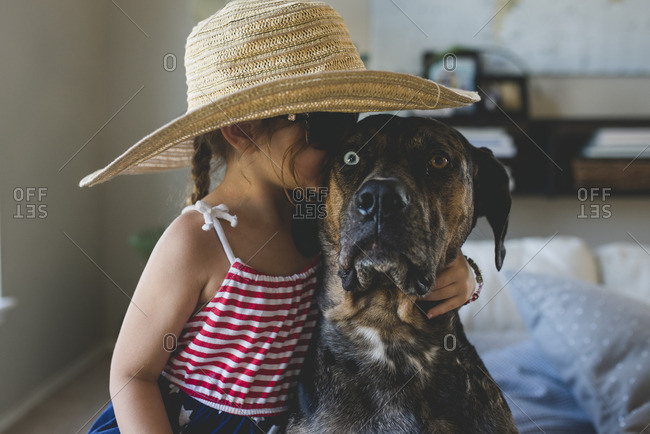 Girl in hat kissing dog
