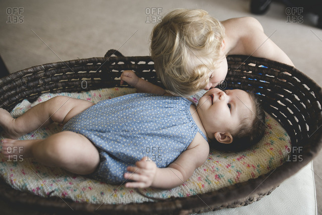 Boy kissing baby in bassinet