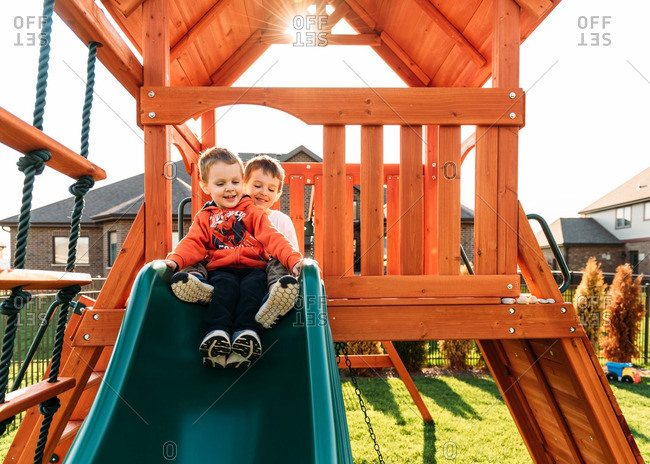 Little brothers sliding down a slide together