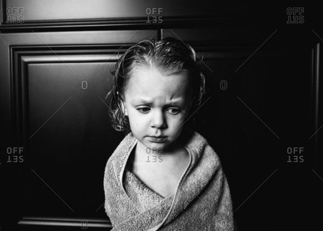 Little boy wrapped in towel looking concerned