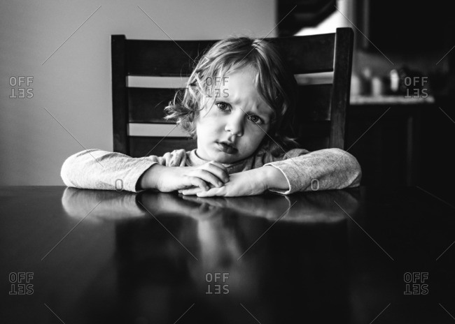 Little boy sitting at a table looking confused