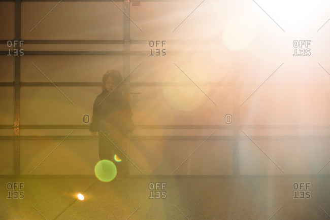 Boy standing by garage door with lens flare