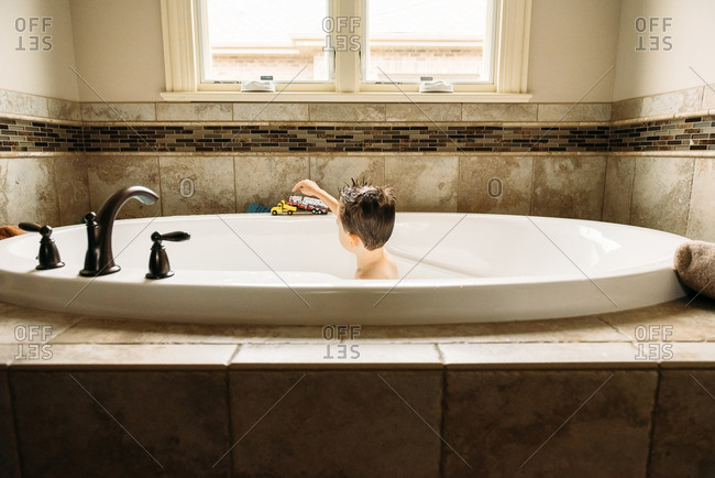 Boy playing with toy trucks in the bathtub