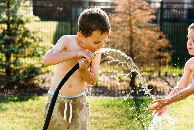 Boys playing with a garden hose and taking a drink