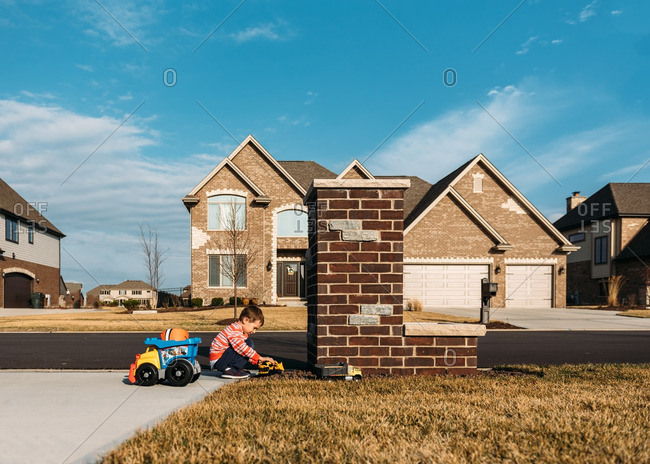 Little boys playing with toy trucks in driveway