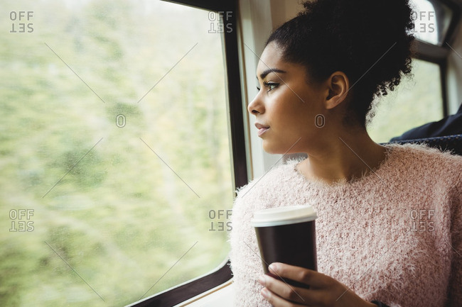 Woman holding disposable coffee cup in train