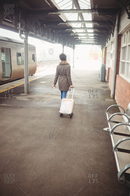 Rear view of woman carrying luggage at railroad station platform
