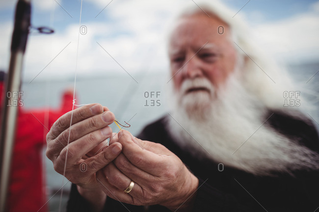 Fisherman adjusting fishing hook