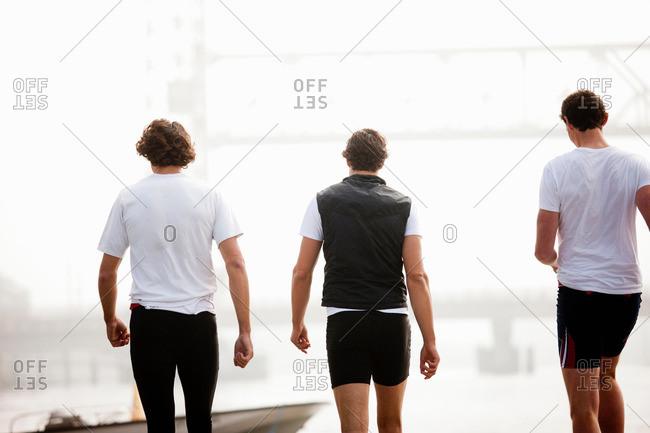 Back view of men walking to boat