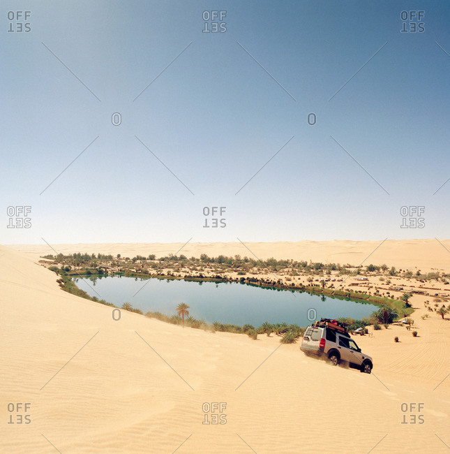 Libya - June 17, 2013: A 4x4 descends a sand dune by Gebraoun Lake, part of the Ubari lakes in the Sahara Desert