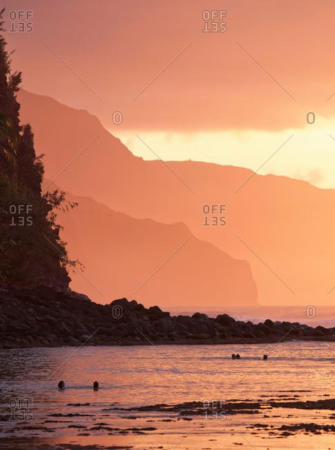 People swim at dusk at Ke'e Beach, Ha'ena State Park, Kauai, Hawaii