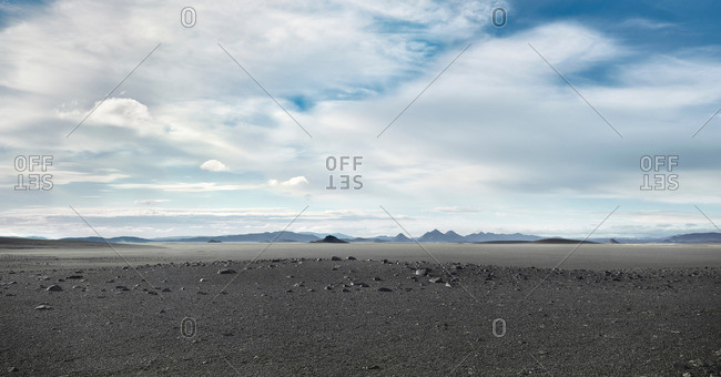 Grey barren landscape under cloudy sky