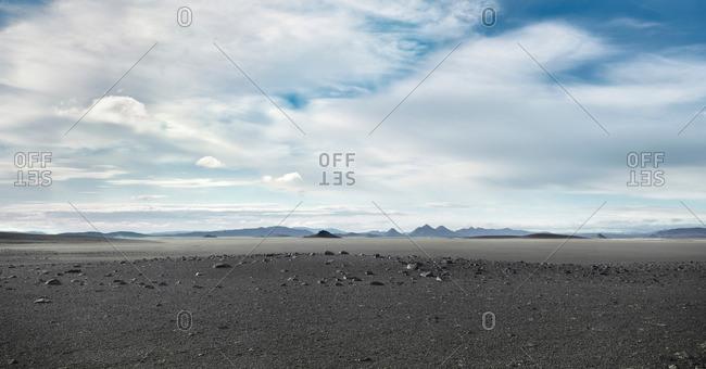 Grey barren landscape under cloudy sky