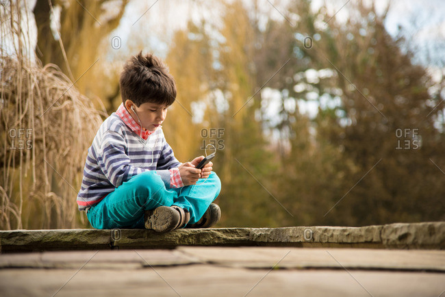 Boy playing on smartphone in playground