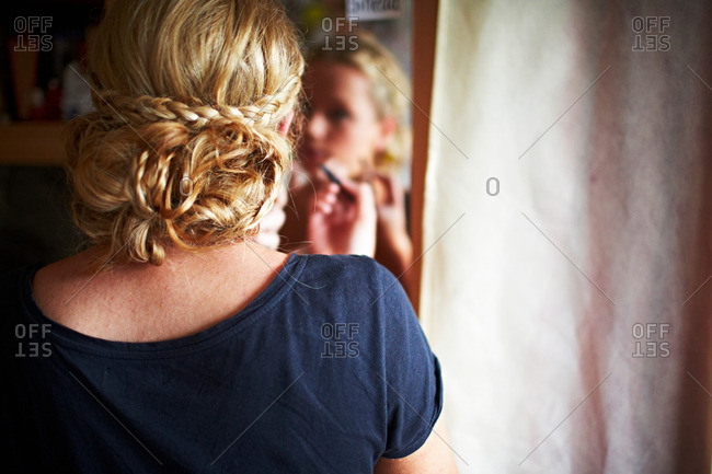 Blonde woman with plaits applying make up in mirror