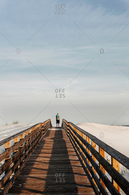 Young man on elevated wooden walkway, Gulf Coast, Alabama, USA