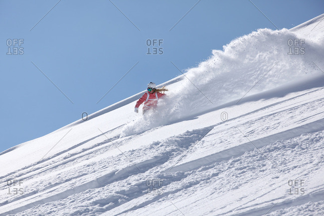 Young woman snowboarding down steep mountain, Hintertux, Tyrol, Austria