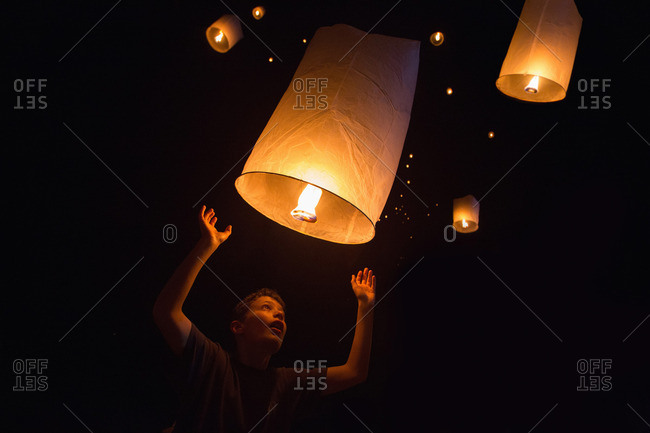 Portrait of boy releasing Chinese lanterns on New Year's Eve, Krabi, Thailand, Southeast Asia