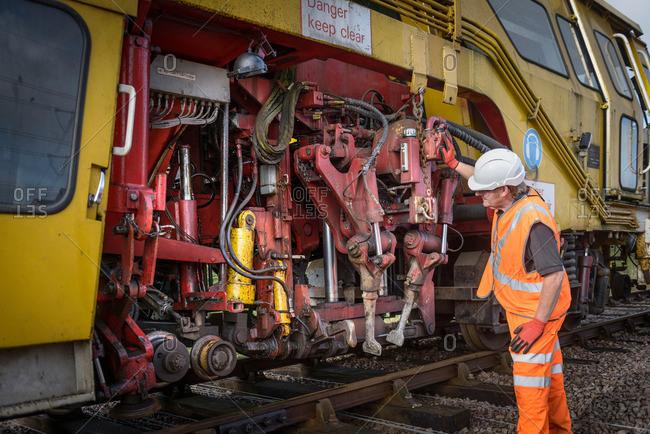 Railway worker inspecting tamping machine on railway