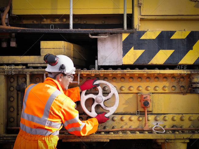 Railway worker turning wheel on maintenance train on railway