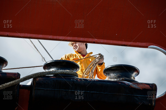 Larnaca, Cyprus - December 11, 2014: Worker fastening ropes to mooring posts on board oil tanker