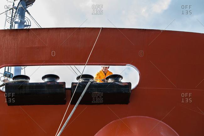 Larnaca, Cyprus - December 11, 2014: Worker fastening ropes to mooring posts on oil tanker deck