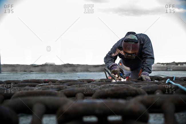 Dock welder welding chain on waterfront pier
