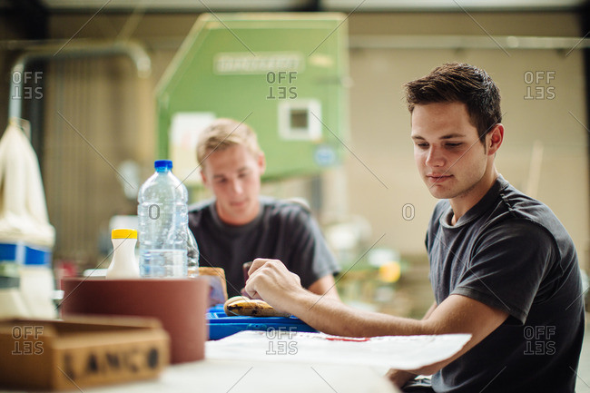 Young male carpenter glancing at blueprint during break in workshop