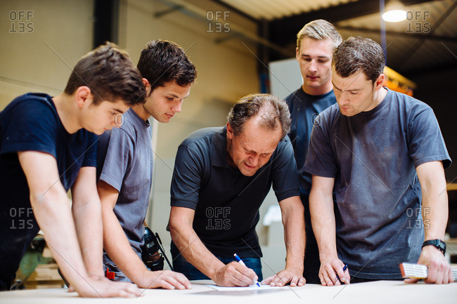 Male carpenter explaining blueprint to young male trainees in workshop