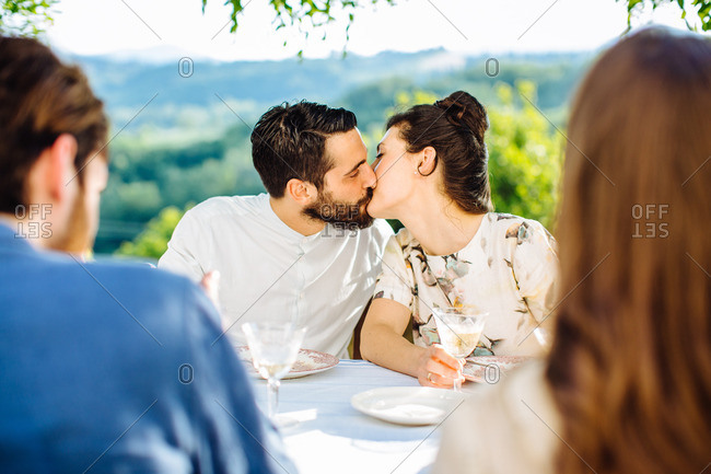 Group of friends having meal together, couple kissing, outdoors