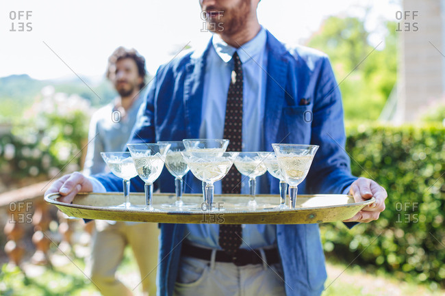 Man carrying tray of drinks outdoors