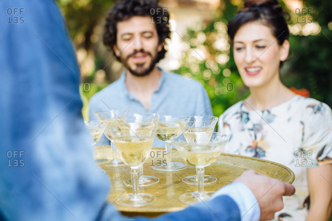 Man carrying tray of drinks outdoors, offering to friends