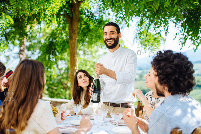 Group of friends having meal together, outdoors, man opening champagne